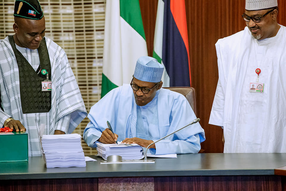 Image of President Buhari signing the budget